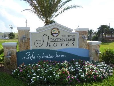 The stone & stucco, lighted city entryway sign, flowers planted below. City seal, name, & logo