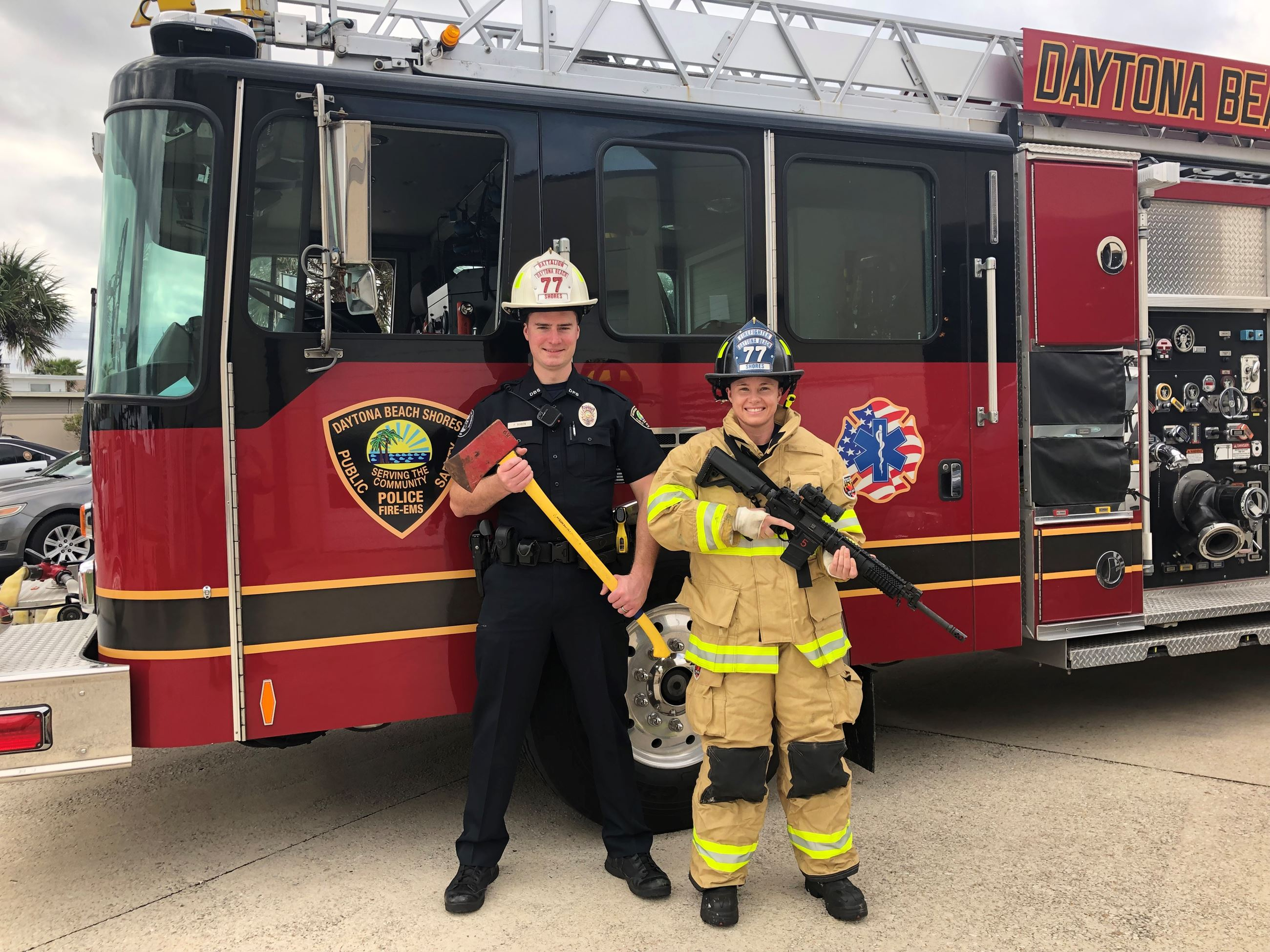 A firetruck with an officer holding an axe and a firefighter holding a gun